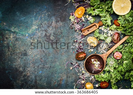 Fresh vegetables cooking ingredients with kale , lemon and tomatoes on rustic background, top view, border. Healthy food or diet nutrition concept