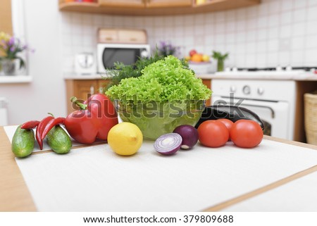 Fresh vegetables for salad on a kitchen table.
