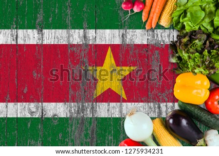 Fresh vegetables from Suriname on table. Cooking concept on wooden flag background. #1275934231