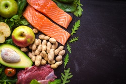 Fresh vegetables, fruits, fish, meat, nuts on black chalk board background. Cauliflower, avocado, apples, tomatoes, salmon, beef, spinach, herbs. Diet/healthy/paleo food. Ingredients. Space for text