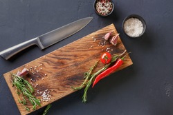 Fresh vegetables, herbs and spices on wood and chef knife on black table surface. Modern restaurant cuisine background with copy space on rustic cutting board, top view