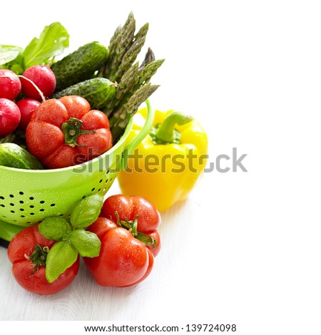 Fresh vegetables in green colander with water drops