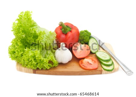 fresh vegetables on a cutting board isolated on white