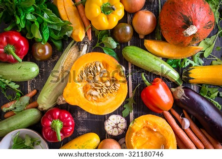 Fresh vegetables on a dark table. Autumn background. Healthy eating. Sliced pumpkin, zucchini, squash, bell peppers, carrots, onions, garlic, tomatoes, eggplant, corn cob, rucola and basil. Top view #321180746