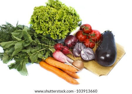 Fresh vegetables on and next to a chopping board: lettuce, tomatoes, carrots, radishes, onions and an eggplant - isolated on white