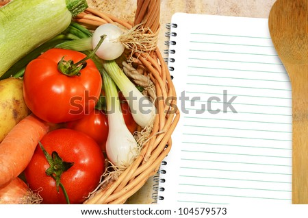 Fresh vegetables on the old tablecloth and paper for notes and recipes