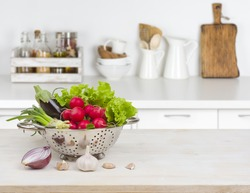 Fresh vegetables on wooden table over blurred kitchen counter interior.