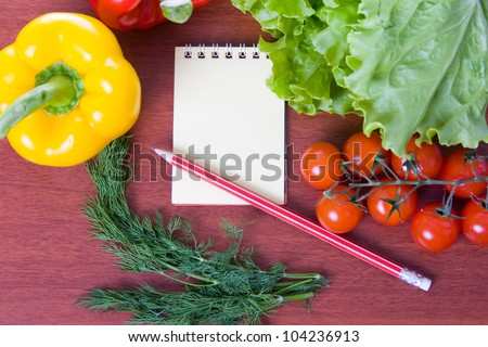 Fresh vegetables,pasta and a notebook on a wooden table