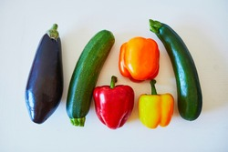 Fresh vegetables prepared for cooking on kitchen table. Ripe organic eggplant, bell pepper and zucchini on white background