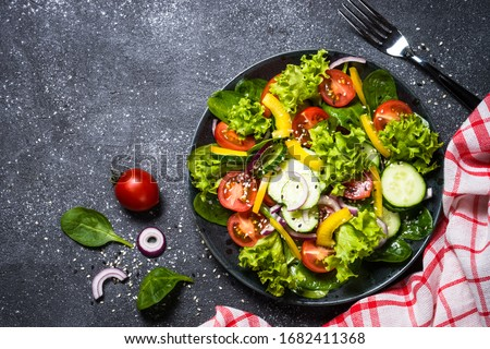 Fresh vegetables salad from cucumber, tomato, spinach, lettuce, onion and paprika in craft black plate. Top view on black background.