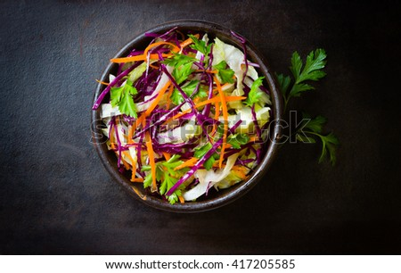 Fresh vegetables salad with purple cabbage, white cabbage,  lettuce, carrot in dark clay bowl on black background. Top view