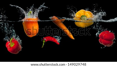 Fresh vegetables splashing in water on black background