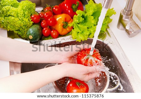 Fresh vegetables under water stream in colander