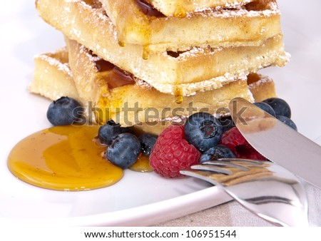 Fresh waffles with blueberries, raspberries and syrup on a plate