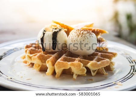Fresh waffles with ice cream and maple syrup  on a wooden background