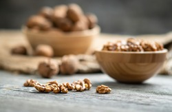 Fresh walnut kernels and whole walnuts in a bowl on rustic old wooden table. Healthy organic food, BIO viands, natural background. Copy space for your advertising text message.