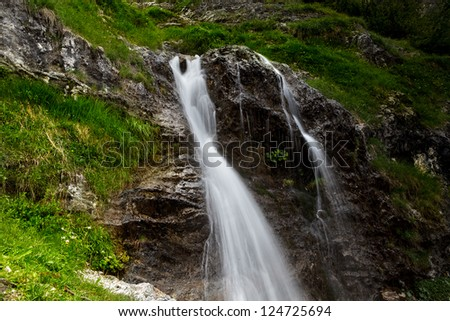 fresh water flowing in a small clear alpine mountain creek