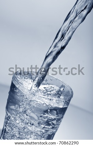 Fresh water pouring into glass over gradient background