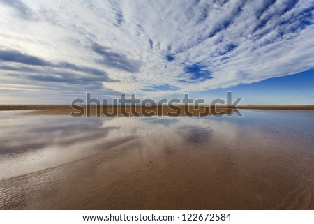 fresh water shallow lake transparent sandy bottom with cloudy blue sky reflection at horizon vast area sea shore