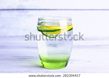 Fresh water with lemon and cucumber in glass on wooden background