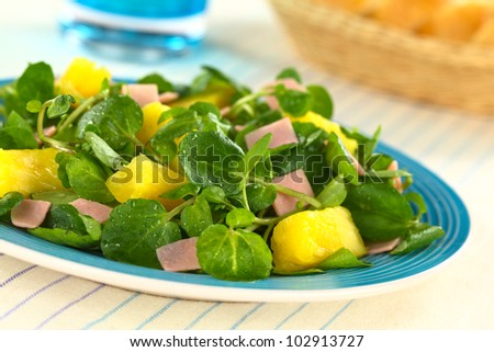 Fresh watercress, pineapple and ham salad on blue plate with bread basket and glass in the back (Selective Focus, Focus on the pineapple pieces in the front)