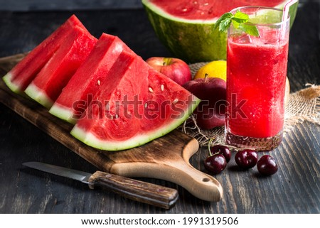 Fresh watermelon juice with ice in a glass. Slices of watermelon on the table.Fresh watermelon juice with ice in a glass. Slices of watermelon on the table.