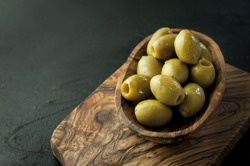 Fresh wet olives in a wooden bowl on the olive wood tree board. Black background. Space for text