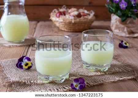 Fresh whey in two glasses and a jug, with pansy flowers in the background