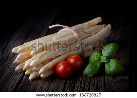 Fresh white asparagus bunch, tomatoes and basil composition. Spring vegetables tied with a string taken on white background.