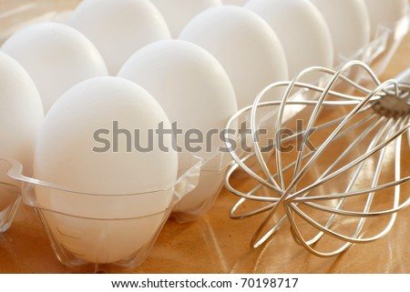 Fresh white eggs with stainless steel whisk.  Macro with shallow dof.