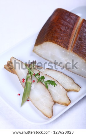 Fresh white fish decorated with salad and condiment. Close-up