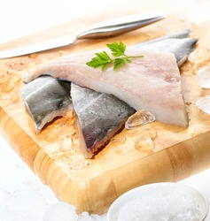 Fresh white fish fillets displayed on chopping board with crushed ice, knife, cracked rock salt and parsley garnish