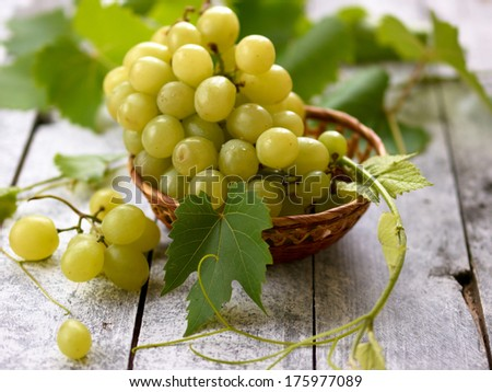 Fresh white grape in basket on wooden background with selective focus