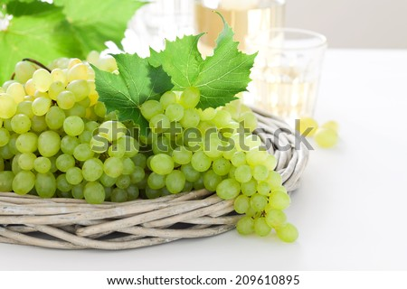 Fresh white grapes in basket and wine on the table, selective focus
