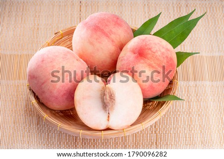 Fresh White Peach fruits with leaves on bamboo mat, Korean white peach in Bamboo basket on wooden bamboo table.