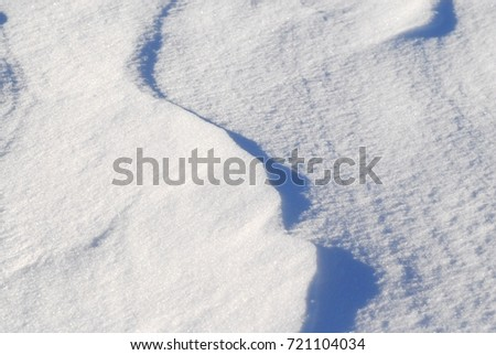 Fresh white snow drift background texture showing contours and shadows. #721104034