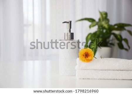 Fresh white towels folded on white table, orange flower and liquid soap container with green leaves of house plant and tulle window on background. Spa and wellness or beauty salon concept. Copy space. Photo stock ©