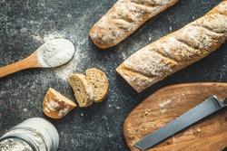 Fresh whole grain bread baguette on black table. Top view.