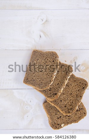 Fresh whole grain bread on white wood background #584126380