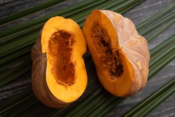 Fresh whole pumpkin vegetable cut in half , large raw ripe orange pumpkin sliced isolated on palm leaves. winter squash from farm harvested in Kerala India