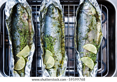 Fresh whole trout fishes richly decorated and marinated being grilled on an electric barbecue