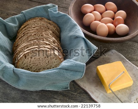 Fresh whole wheat bread in a basket, cheddar cheese and brown eggs in the background on a rustic wooden table