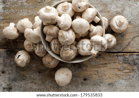 Fresh whole white button mushrooms, or agaricus, in a bowl on a rustic wooden counter ready to be cleaned and washed for dinner, overhead view