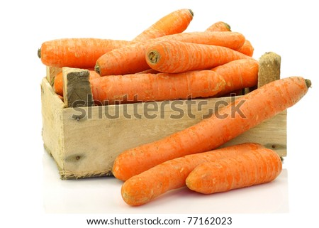fresh winter carrots in and around a wooden box on a white background - stock photo
