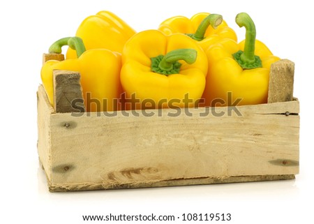 fresh yellow bell peppers (capsicum) a in a wooden crate on a white background