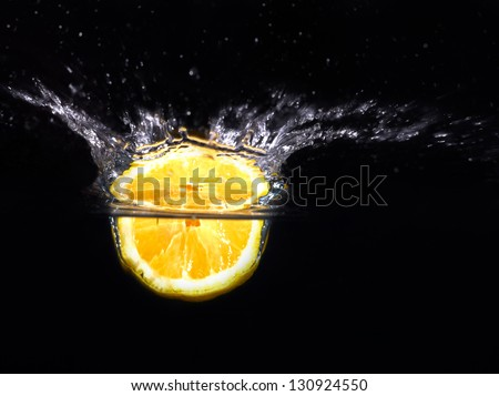 Fresh yellow lemon falling into the water with a splash of water. On a black background