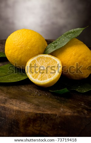 fresh yellow lemons with leaves and water drops on wooden table