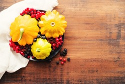 Fresh yellow squash and berries of viburnum and chokeberry on a round plate on a wooden brown board, top view, copy space. Autumn or Thanksgiving background.