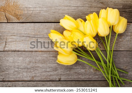Fresh yellow tulips bouquet over wooden table background