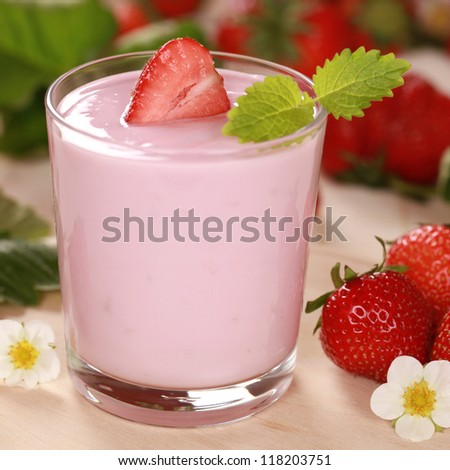 Fresh Yogurt in a glass with strawberries, leaves and blossoms